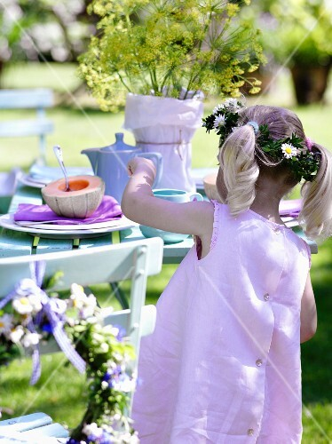 A girl wearing a pink dress and a crown of flowers by a table in a garden
