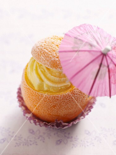 A frosted orange with orange and passion fruit ice cream and a cocktail umbrella