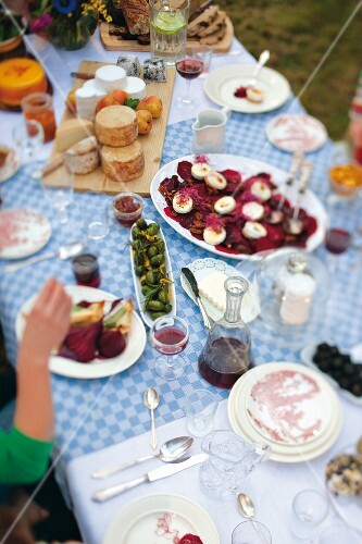 A table laid outside with canapés, cheese and wine