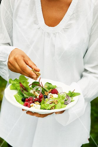 A mixed leaf salad with berries, goat's cream cheese and oats