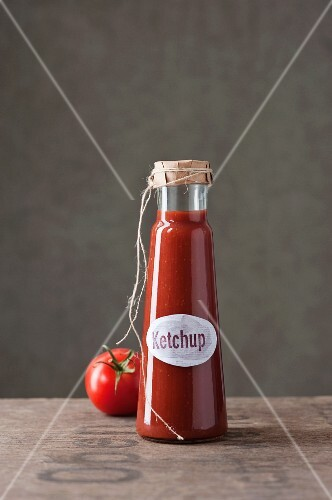 A bottle of homemade ketchup and a tomato