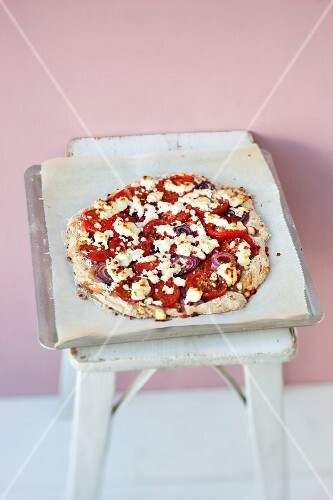 A wholemeal pizza with tomatoes, goat's cream cheese and honey
