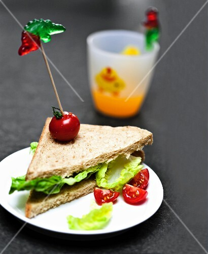 A sandwich with lettuce, tomatoes and gummy sweets on skewers