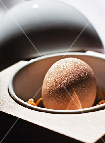 A chocolate ball filled with coconut and mango mousse