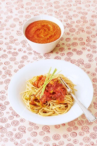 A bowl of baby food and a plate of spaghetti with vegetable bolognese