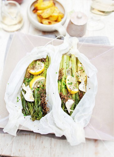 Gratinated green asparagus with lemons and garlic in parchment paper