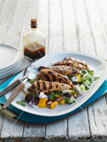 Grilled chicken breast on a bed of Greek salad