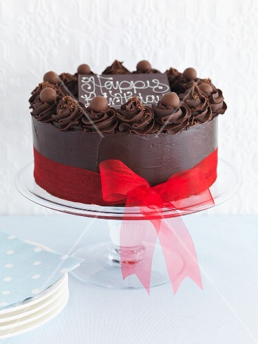 A chocolate cake with a ribbon and the word Happy Birthday