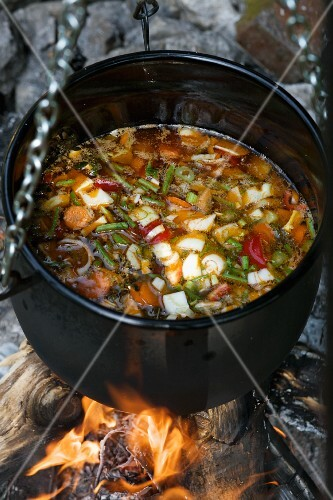 Vegetable soup in a cauldron over a camp fire