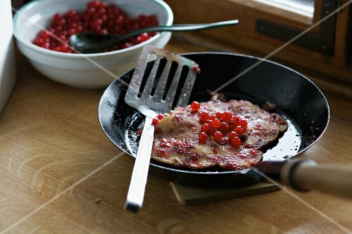Pancakes with redcurrants in a pan