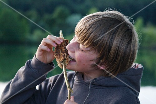 A boy eating stick bread