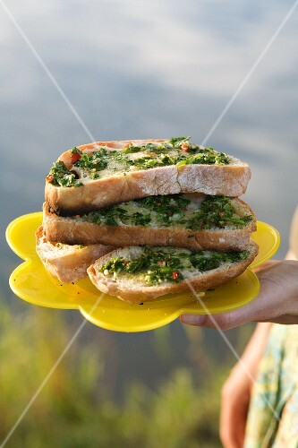 Herb bruschetta on a yellow plastic plate