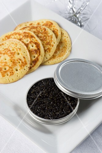 Black caviar in a tin with corn pancakes