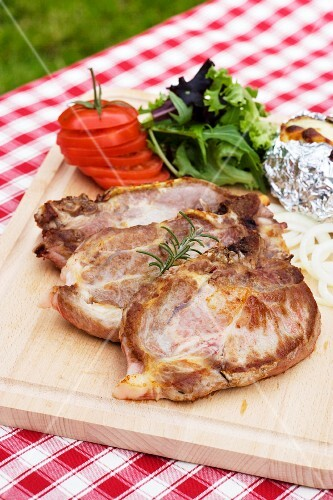 Grilled pork chops with sides on a chopping board