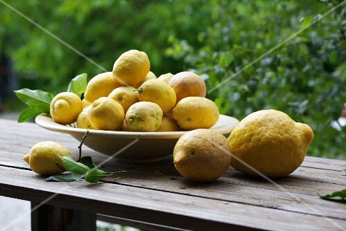 Lemons in a bowl on a wooden bench in the open air