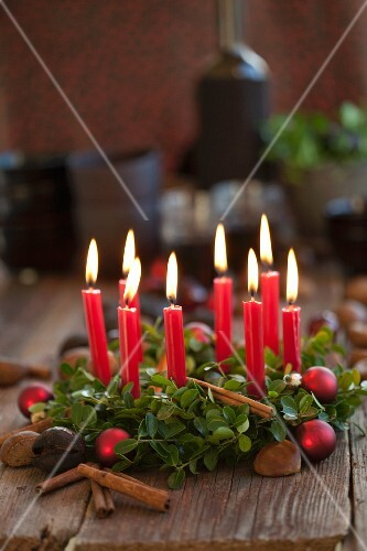 A box wreath with candles, chestnuts, cinnamon sticks and Christmas baubles