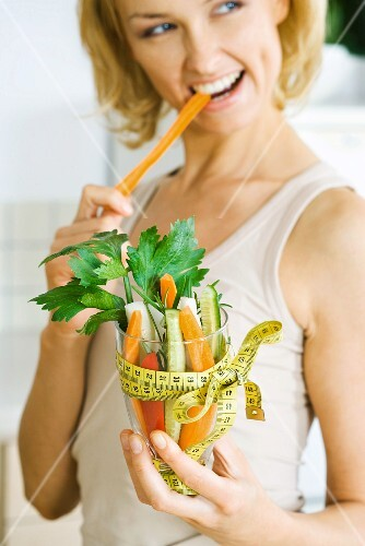 Woman biting into carrot, holding glass full of vegetables tied with measuring tape