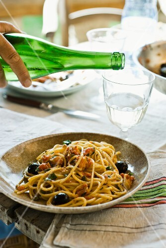 Spaghetti alla puttanesca with olives (pasta dish with olives and capers)