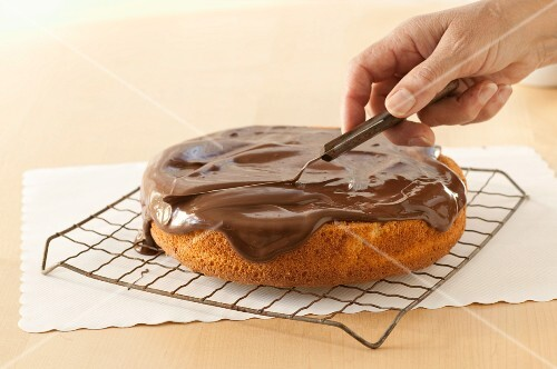 Spreading Frosting on a Single Layer Gluten Free Yellow Cake; On Cooling Rack,