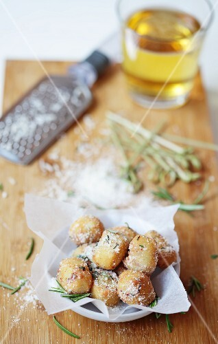 Deep-fried cheese balls with a glass of beer in the background