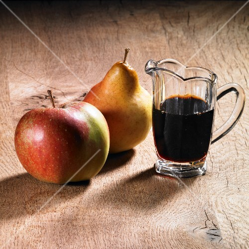 A jug of apple and pear syrup with an apple and pear