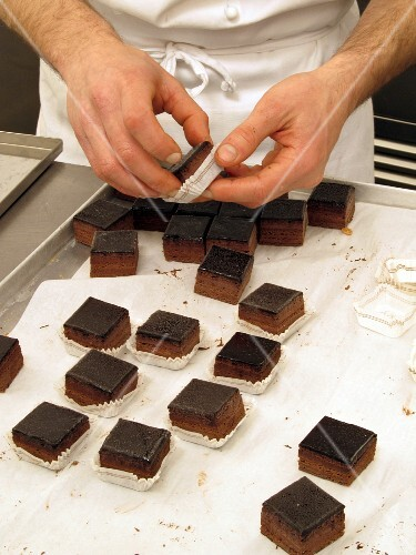 Chocolate cubes being added to praline cases