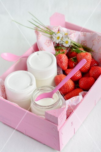 Homemade natural yogurt in jars with fresh strawberries