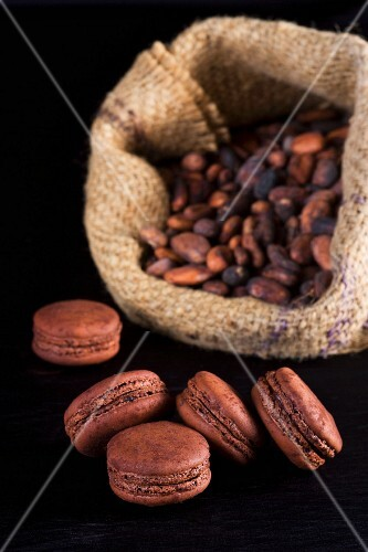 Chocolate macaroons with cocoa beans in the background