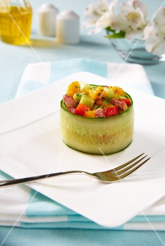 A stuffed cucumber roll filled with mango salad, pepper, cucumber and bacon