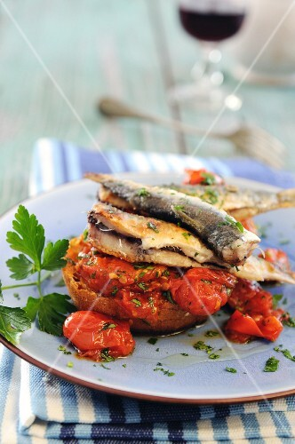 Crostini topped with sardines and tomatoes
