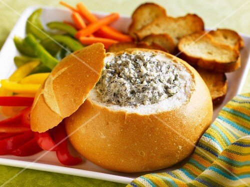 Spinach Dip in a Bread Bowl with Sliced Veggies and Toasted Bread Slices for Dipping