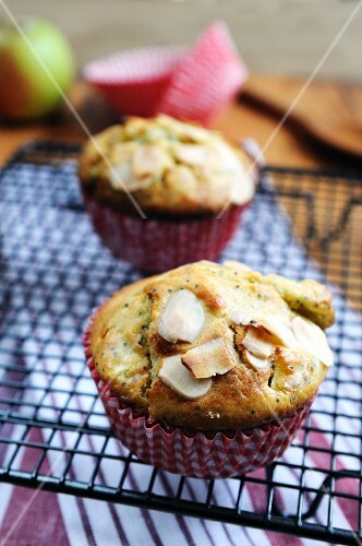 Apple muffins with poppy seeds and almonds on a wire rack