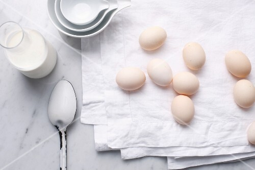 Eggs, milk and spoon on table