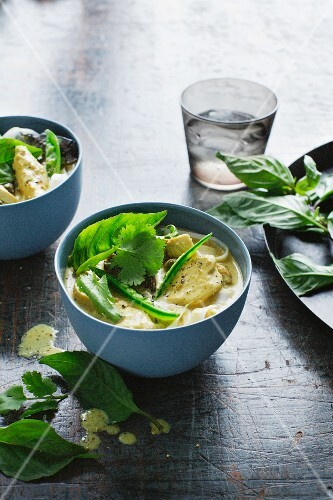 Bowls of chicken laksa and herbs