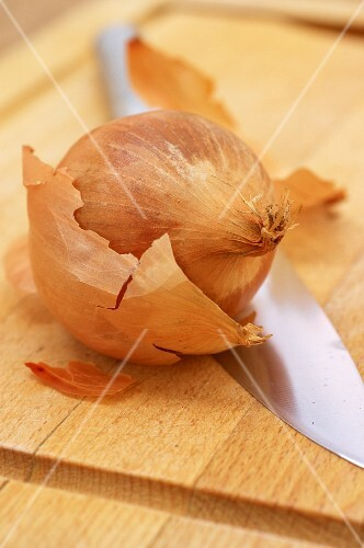 A onion and a knife on a wooden chopping board