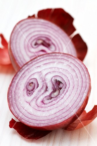 A red onion, halved, with skin