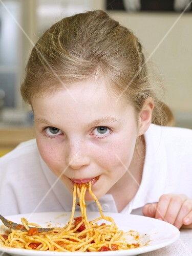 A girl eating pasta