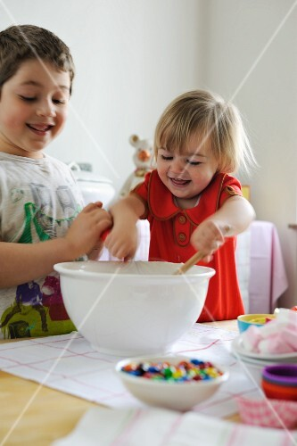 Young boy and girl mixing ingredients for cupcakes in a bowl