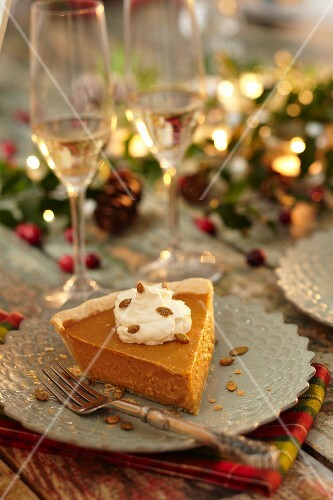 Slice of Pumpkin Pie Topped with Whipped Cream in a Holiday Party Setting