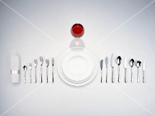 Plates, cutlery, a napkin and a glass of red wine