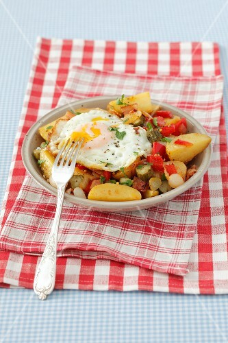 Fried potatoes with pancetta, peppers, gherkins and a fried egg