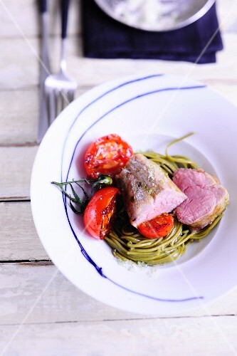 Veal fillet on a bed of noodle with tomatoes