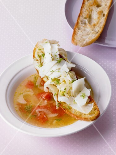 Fennel soup with tomatoes served with crostini topped with fennel and manchego cheese