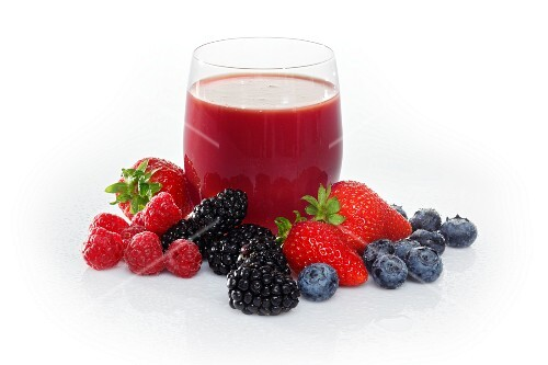 A glass of fruits of the forest juice surrounded by fruits of the forest