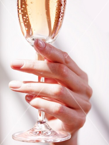 A hand holding a glass of champagne