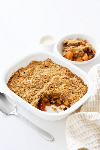 Apple crumble in the baking dish and a small bowl
