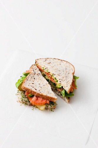 Sandwich with smoked salmon and sprouts in front of white background