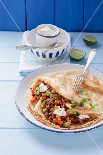 A pancake with minced meat, sour cream and avocado
