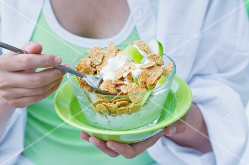 A girl eating cornflakes with yogurt and apple