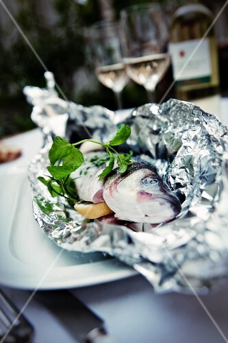 Trout wrapped in aluminium foil with lemon and basil